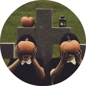 Creepy Girls Holding Pumpkins in Cemetery with Cross Headstones