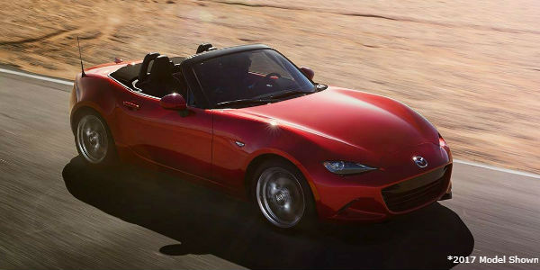 Red 2017 Mazda MX-5 Miata Convertible with Top Down on Track in Desert with Asterisk and 2017 Model Shown