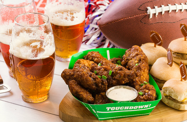 Close Up of Wings, Beers, Burgers and a Football on a Table at a Party
