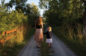 Mother and Daughter Holding Hands and Walking on a Dirt Road in the Woods