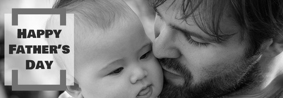 Black and White Photo of Father Holding Child with Black Happy Father's Day Text