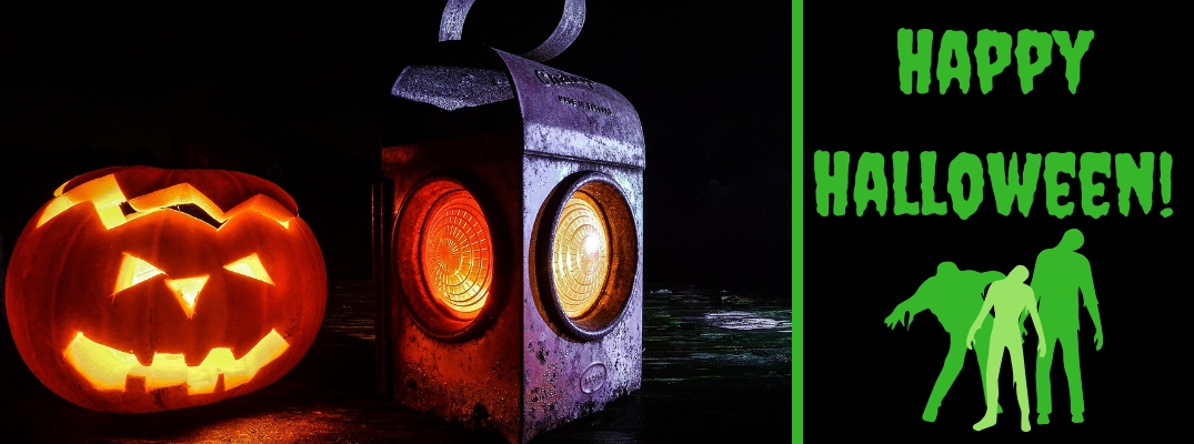 Picture of a Lit Jack-o-Lantern and Lantern on a Table and Black Background with Green Happy Halloween Text with Green Cartoon Zombies