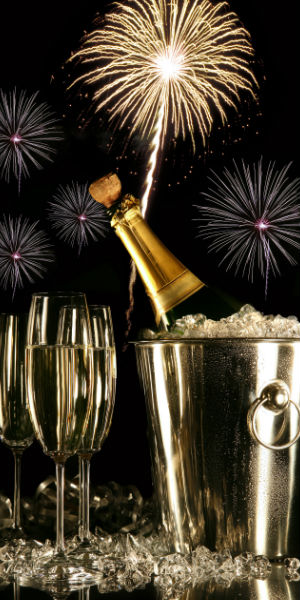 Black Background with Fireworks, a Champagne Bottle in a Bucket and Full Champagne Glasses