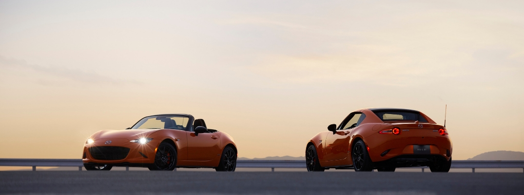 Two Racing Orange 2019 Mazda MX-5 Miata 30th Anniversary Edition Models on a Track at Sunset