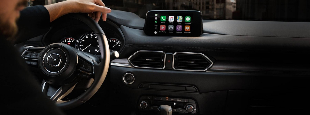 Man Behind the Wheel of a 2019 Mazda CX-5 with Apple CarPlay Menu on the Touchscreen