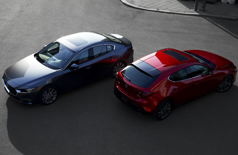 Overhead View of Gray 2019 Mazda3 Sedan and Red 2019 Mazda3 Hatchback in a Driveway