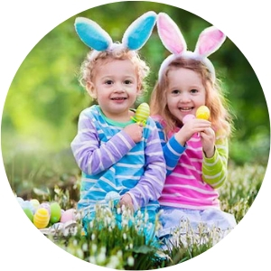 Two Little Girls with Easter Bunny Ears on Sitting in Grass with an Easter Basket and Easter Eggs