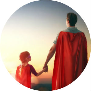Father and Daughter Holding Hands and Wearing Red Superman Capes
