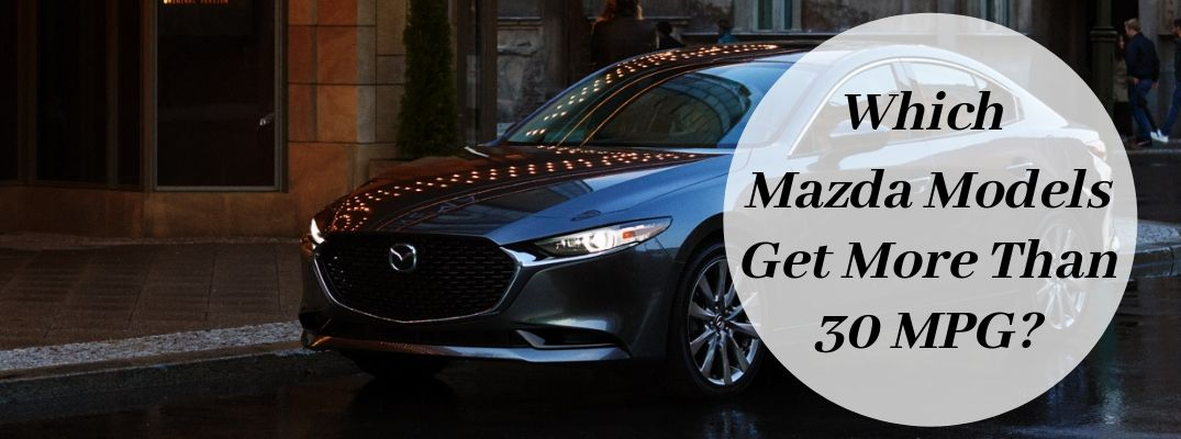 Gray 2019 Mazda3 on a City Street with a White Circle and Black Which Mazda Models Get More Than 30 MPG? Text