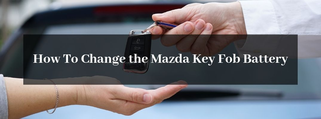 Man Putting a Key Fob in a Woman's Hand with Black Text Box and White How To Change the Mazda Key Fob Battery Text