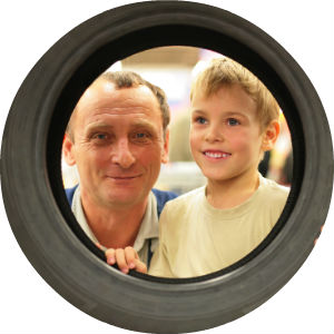 Child and Mechanic Looking Through a Tire