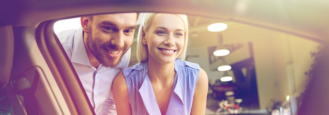 Young Couple Looking in the Window of a New Car