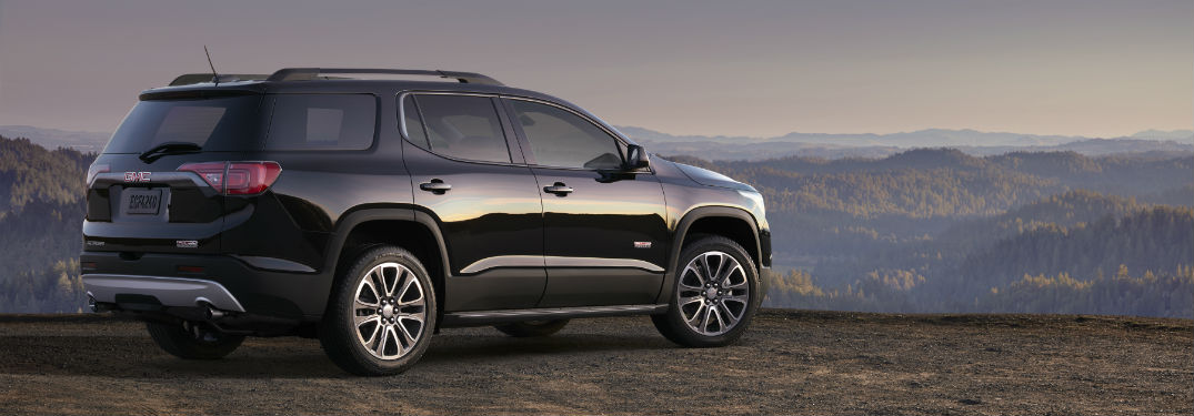 Passenger side exterior view of a black GMC Acadia overlooking mountains