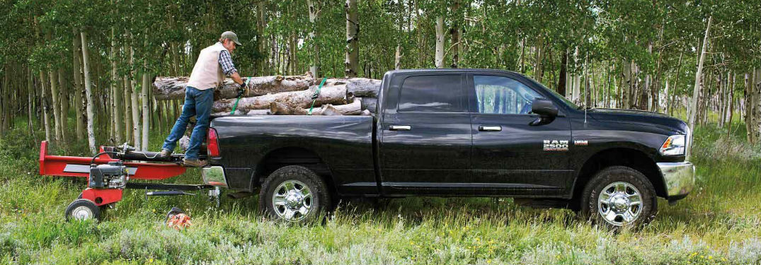 Man loading logs into the bed of the 2018 Ram 2500