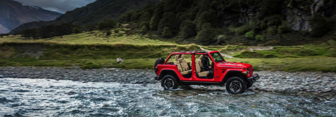 Red 2018 Jeep Wrangler driving through a stream with doors removed