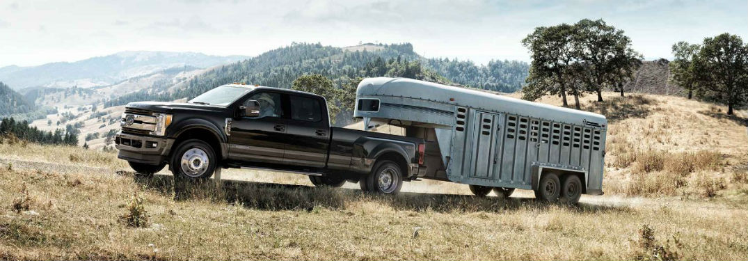 Driver side exterior view of a black 2018 Ford Super Duty F-350 towing a large trailer
