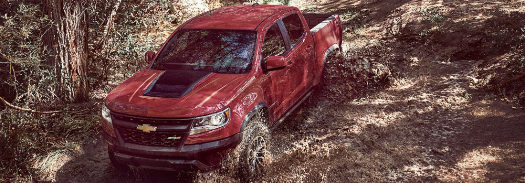 Front exterior view of a red 2018 Chevy Colorado diving through mud