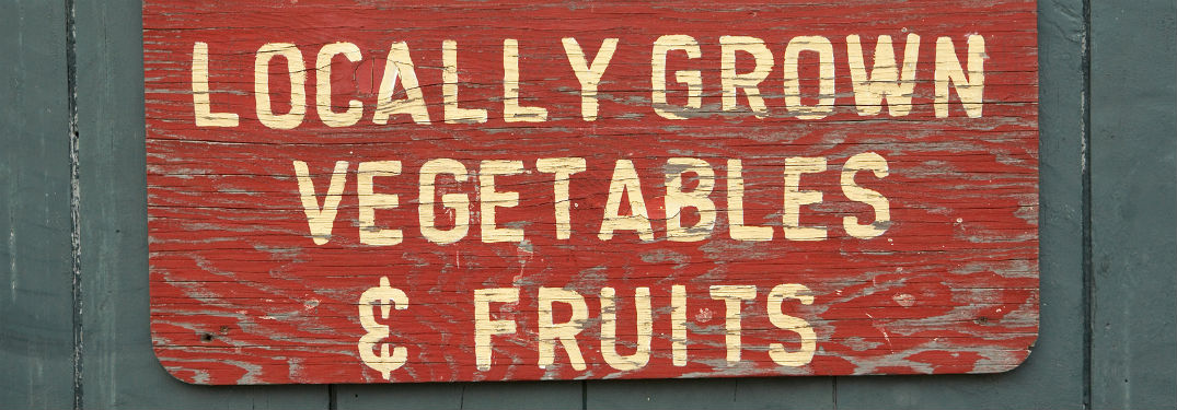Locally grown vegetable and fruits, text on a red wooden background