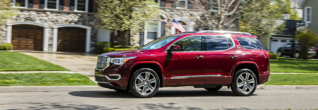 Driver side exterior view of a red 2019 GMC Acadia Denali