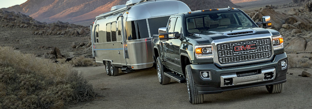 Front exterior view of a 2019 GMC Sierra 2500HD towing a camper