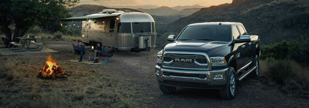 Front exterior view of a black 2018 Ram 2500 parked next to an Airstream trailer