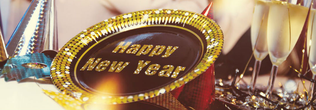 """Happy New Year"" written in gold on a fancy plate on a table next to champagne glasses"