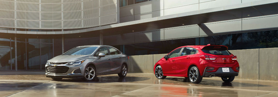 Front driver side exterior view of a gray 2019 Chevy Cruze sedan parked next to a rear driver side exterior view of a red 2019 Chevy Cruze hatchback