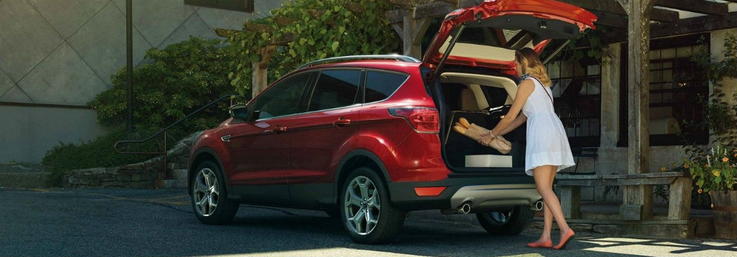 Driver side exterior view of a red 2019 Ford Escape being loaded with cargo