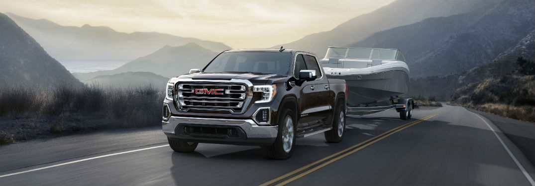 Front driver side exterior view of a black 2019 GMC Sierra 1500 towing a boat