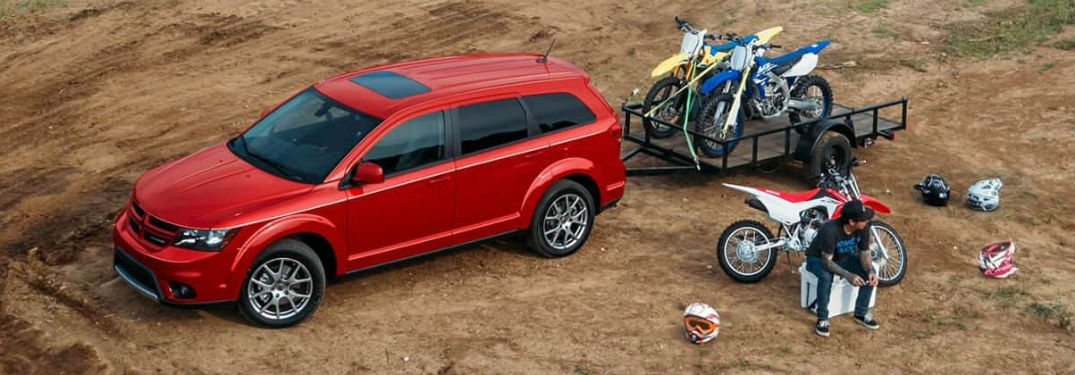 Overhead driver side exterior view of a red 2019 Dodge Journey carrying a loaded trailer of dirt bikes