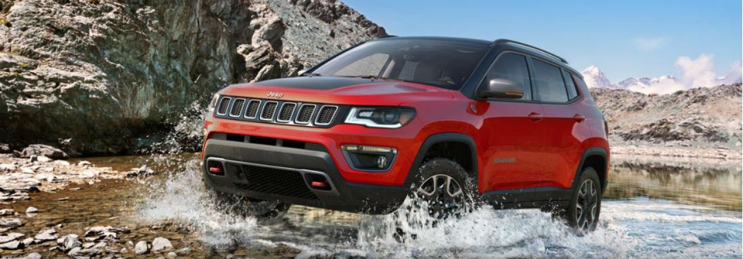 Front exterior view of a red 2019 Jeep Compass driving over a stream
