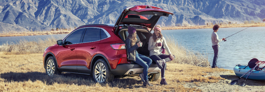 Rear driver side exterior image of a red 2020 Ford Escape with two women drinking coffee on the tailgate