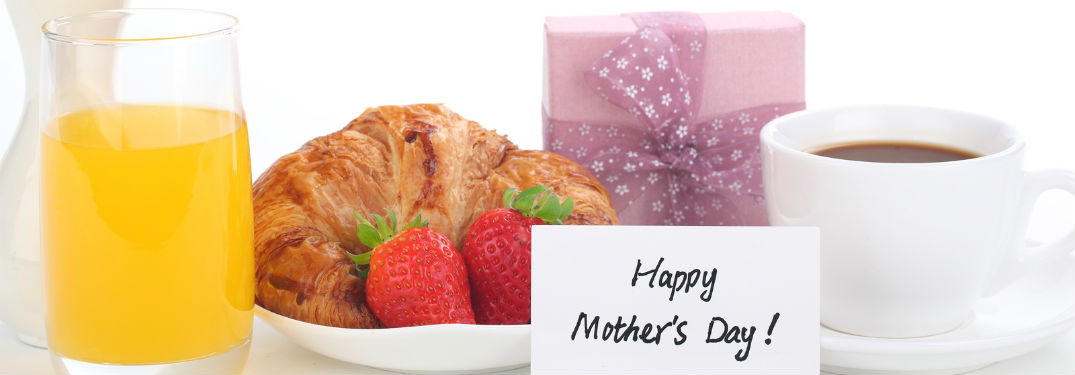 """""""Happy Mother's Day!"""" written on a white place card in front of a plate with a croissant and strawberries as well as a gift wrapped in purple paper and a cup of coffee"""
