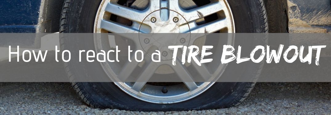 How should you react to a tire blowout while driving?
