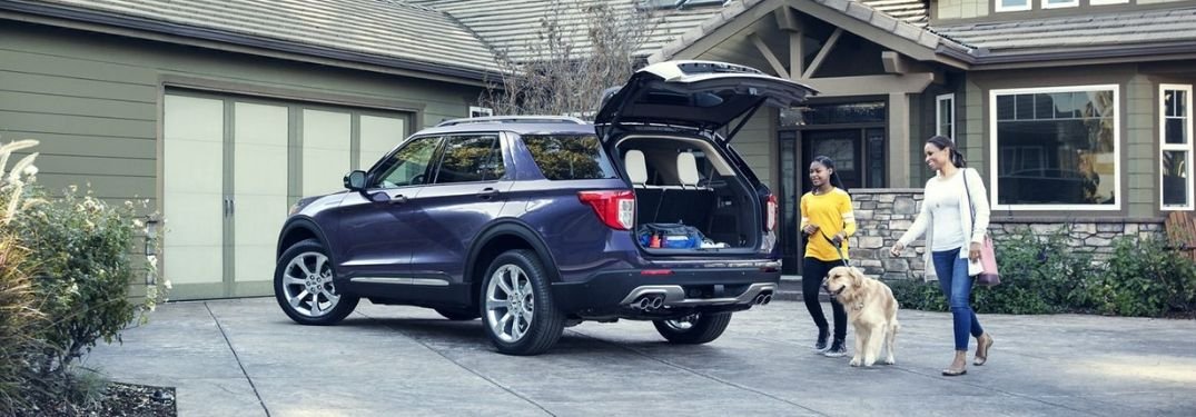 mom and daughter and their dog walking up to the open rear cargo door of the 2020 Ford Explorer