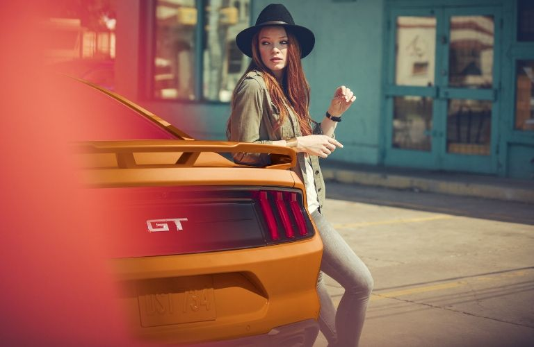 woman leaning against rear of 2020 Ford Mustang