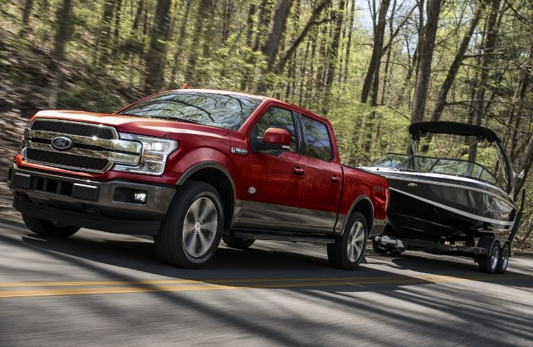 red 2020 Ford F-150 towing a boat on a forest highway