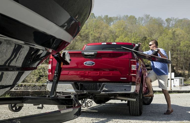 man loading cargo into the truck bed of the 2020 Ford F-150 with a boat attached to the tow hitch