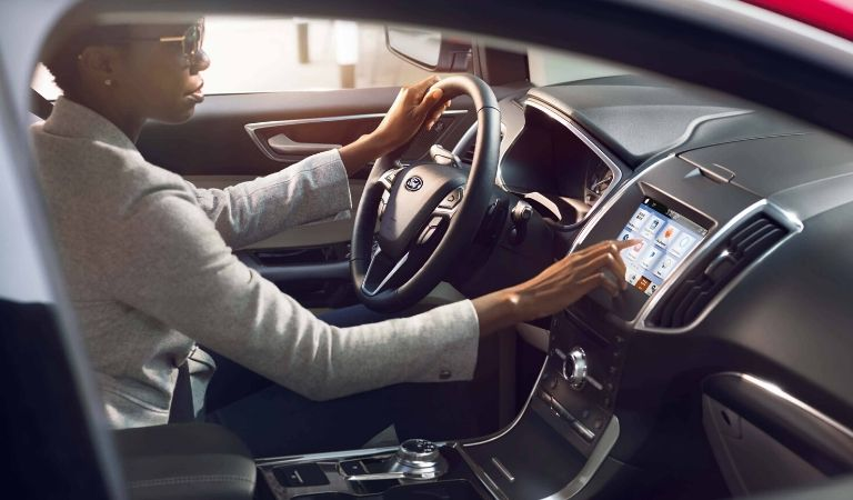 woman driving 2019 Ford Edge and using touchscreen