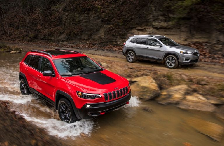 2020 Jeep Cherokee models driving in and along a stream