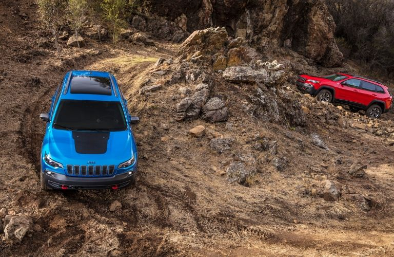 two 2020 Jeep Cherokee models driving over rocky hills