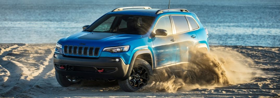 2020 Jeep Cherokee driving on a beach kicking up sand
