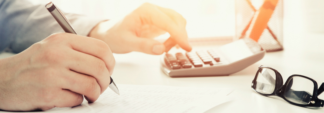 A person using a calculator and filling out a form