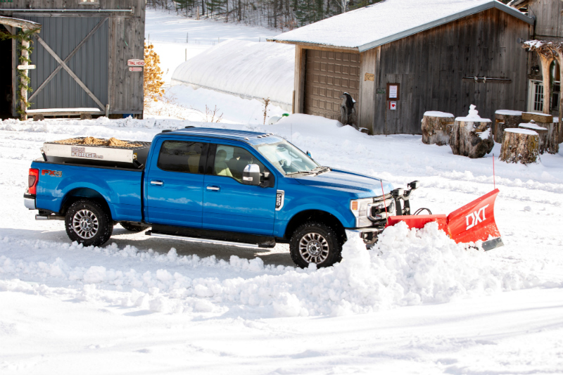 Blue 2020 Ford F-Series Super Duty with Snow Plow Prep Package plowing snow in front of wood buildings