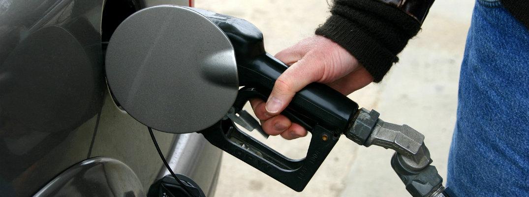 Hand of man using pump to fill up gas tank of vehicle