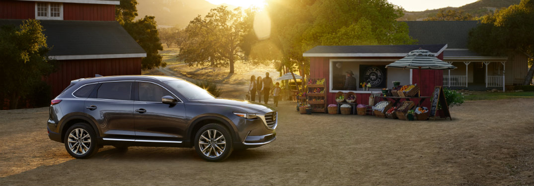 mazda cx9 parked near stand at sunset