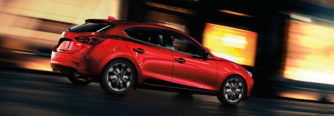 red mazda3 driving in city