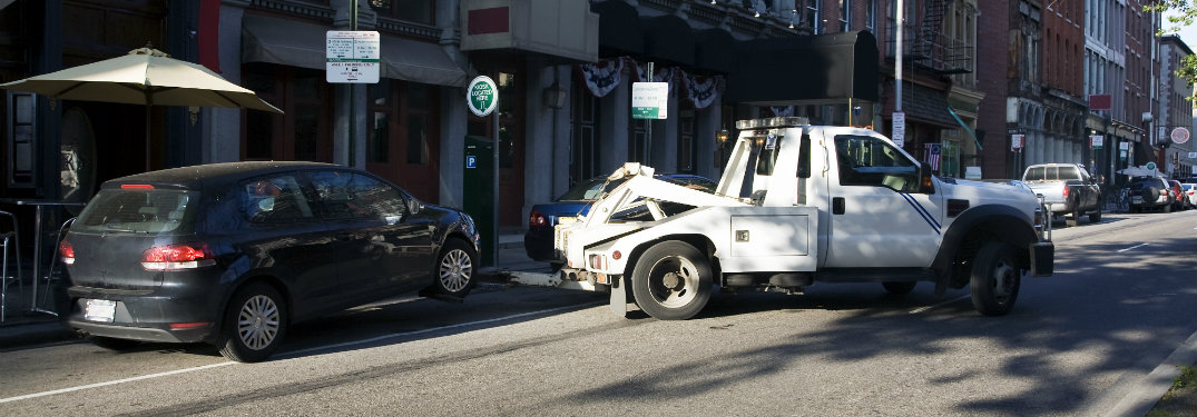 white tow truck pulling black car