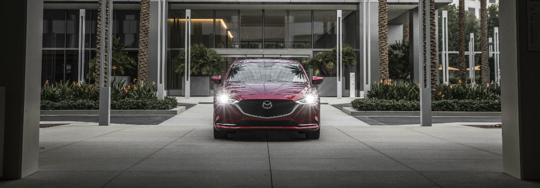 dark red mazda6 with headlights on