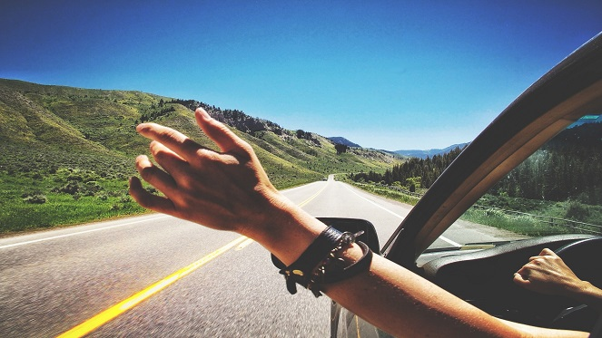 A Lady has her hand out as she enjoys the open road during her road trip